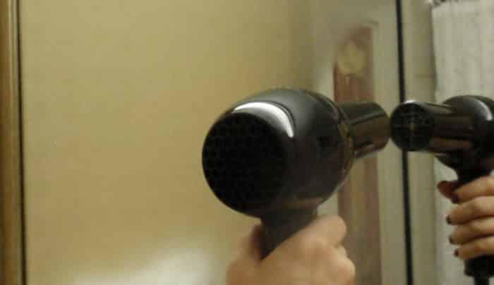 Defogging a bathroom mirror by using hair dryer