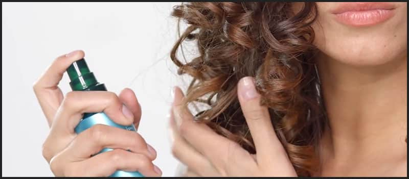 Applying hairspray to curly hair